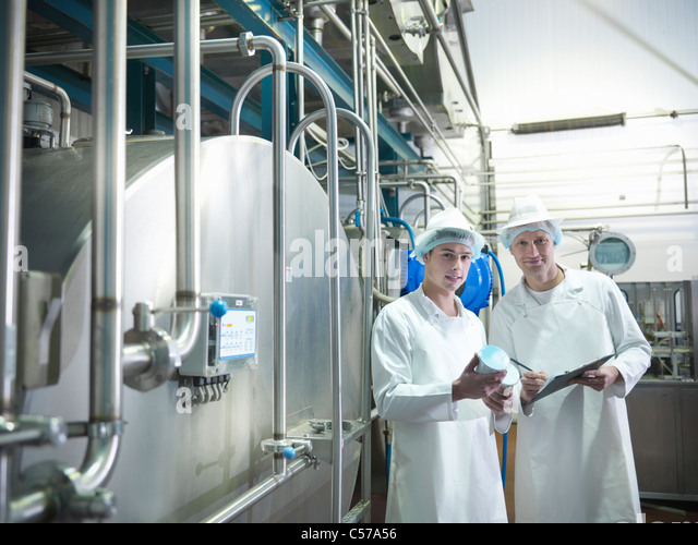 Workers inspecting goat yogurt in dairy - Stock Image