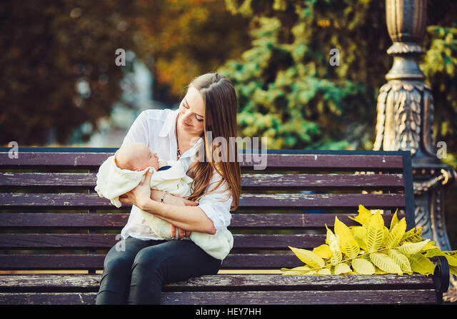 mother and two daughters rest on a bench - Stock Image