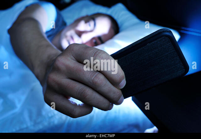 closeup of a young man in bed looking at the smartphone at night - Stock Image