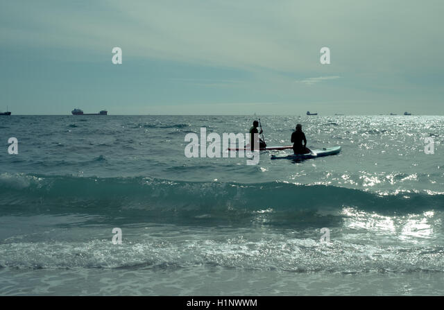 Stand up paddleboarders paddling on their knees off Gyllyngvase Beach, Falmouth, Cornwall with tankers in the far - Stock Image