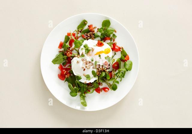 Poached egg watercress tomato salad breakfast - Stock Image