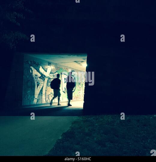 2 teens walking at night in urban city with graffiti - Stock-Bilder