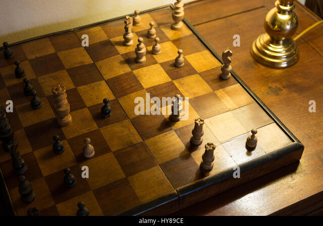 Old chessboard on writing desk and Soft Light of A desk Lamp - Stock Image