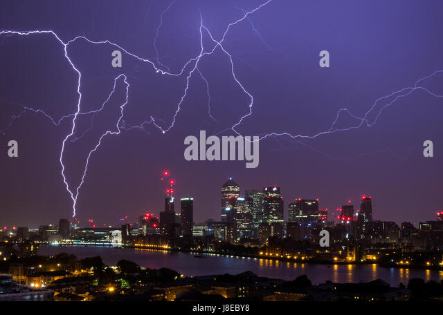 London, UK. 29th May, 2017. UK Weather: Lightning strikes over Canary Wharf business park buildings and River Thames - Stock-Bilder