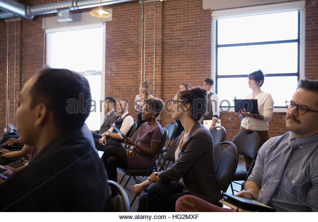 Business people listening in conference room audience - Stock Image