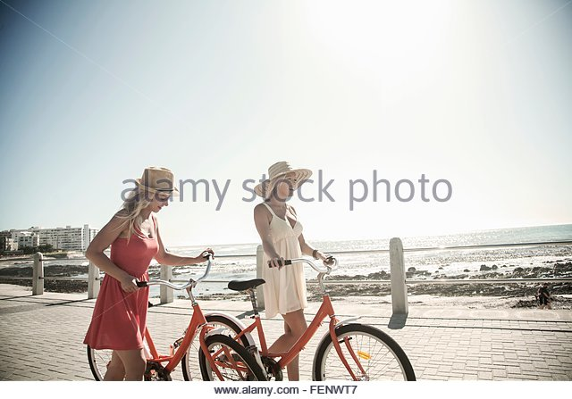 Young women walking with bicycle on seafront, Cape Town, South Africa - Stock Image