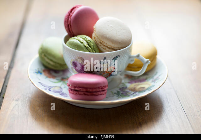 Multi colorered macarons in vintage tea cup, Paris, France - Stock Image