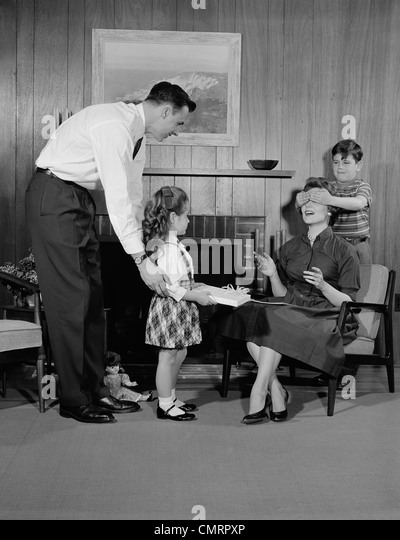 1950s FAMILY LIVING ROOM WOMAN MOTHER GETTING SURPRISE GIFT FROM CHILDREN DAUGHTER SON HUSBAND - Stock Image