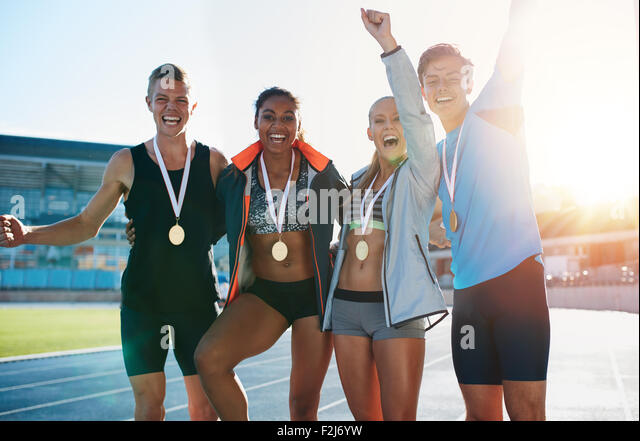 Portrait of ecstatic young athletes together with medals. Group of runners standing together smiling with their - Stock Image