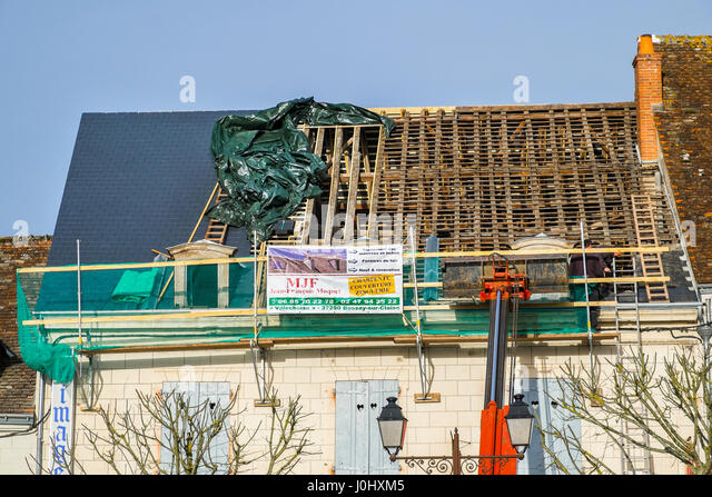 Old roof undergoing renovation with new slates - France. - Stock Image
