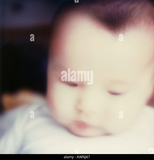 Baby looking down, close-up, blurred. - Stock Image