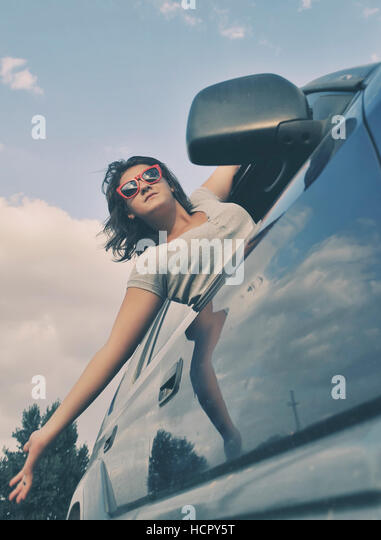 Girl looks out the window when riding in a car - Stock Image