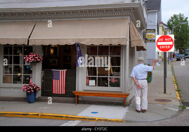 Rhode Island Newport Spring Street business senior man waving small town flag Americana - Stock Image