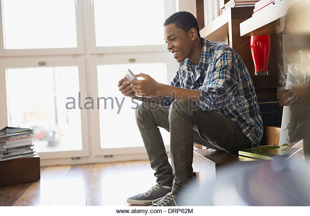 Teen using digital tablet at home - Stock Image