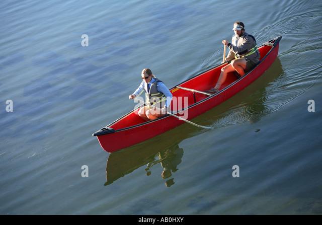Couple paddle canoe on lake - Stock Image