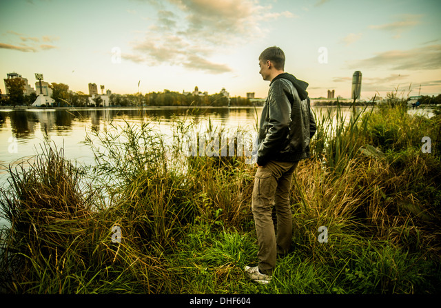 Young man standing on grass looking at water, Russia - Stock Image