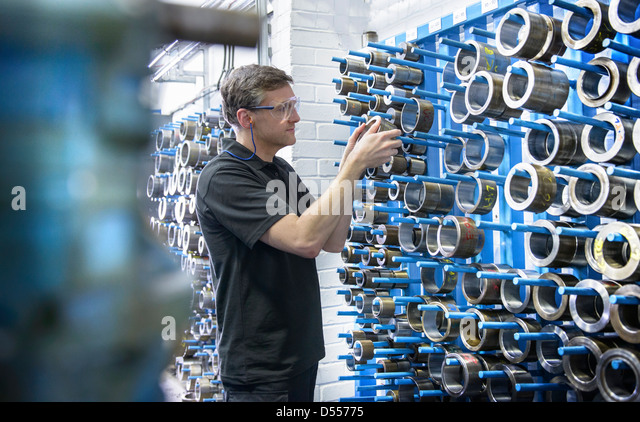 Worker selecting metal coil in factory - Stock Image