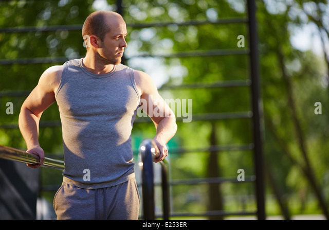 Young man training on sport equipment outside - Stock Image