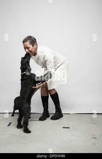 Studio shot of mature woman having fun with pet dogs - Stock Image