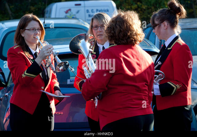 Four women musicians in the red military jackets of a brass band - Stock Image