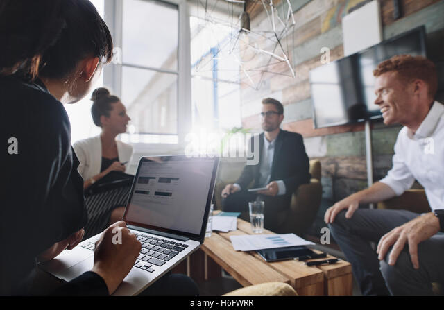 Businesswoman working on laptop while sitting in meeting with colleague. Business people in meeting room. - Stock Image