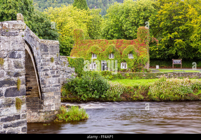 17th century stone bridge over the River Conwy at Llanrwst, with the ivy-clad Tu Hwnt i'r Bont National Trust - Stock Image