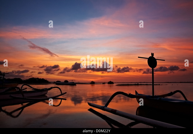 sunset over traditional fishing boats on Bali, Indonesia - Stock Image