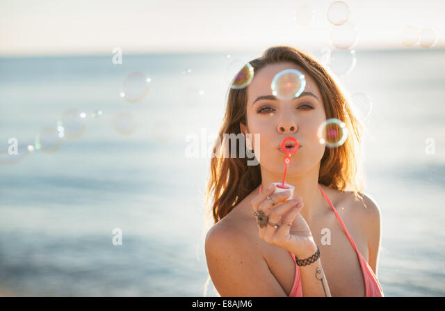 Portrait of young woman on beach blowing bubbles, Castiadas, Sardinia, Italy - Stock Image