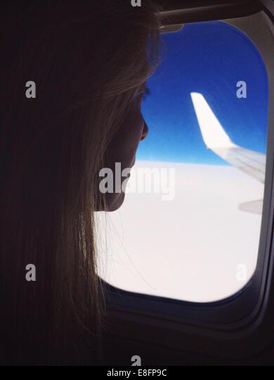 Woman looking out of window on a plane - Stock Image