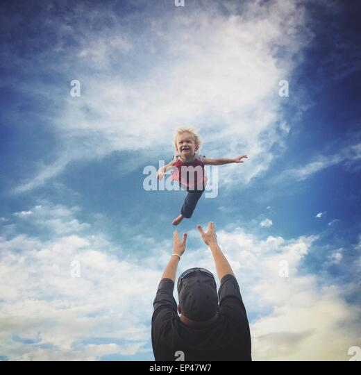 Father throwing his son in the air - Stock Image