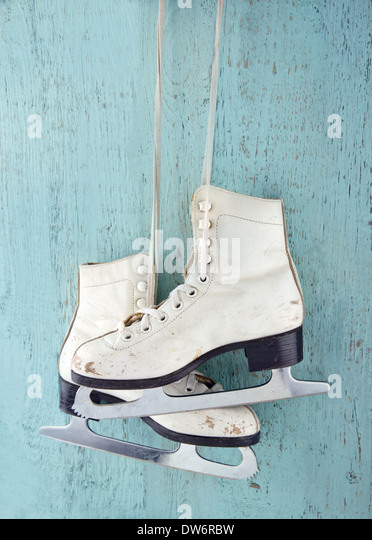 Pair of white women's ice skates on blue vintage wooden background - feminine winter sports concept - Stock Image