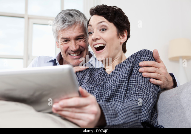 Germany, Bavaria, Munich, Couple using digital tablet at home, smiling - Stock Image
