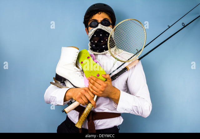 Young man has too many hobbies and recreational pursuits - Stock Image