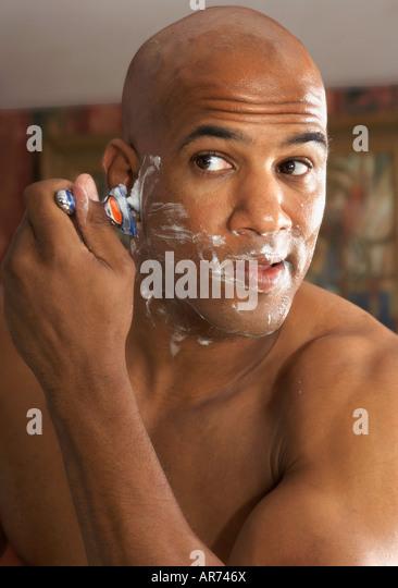 Mixed Race man shaving in mirror - Stock Image