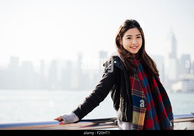 Portrait of young woman wearing checked scarf and leather jacket, looking at camera - Stock Image