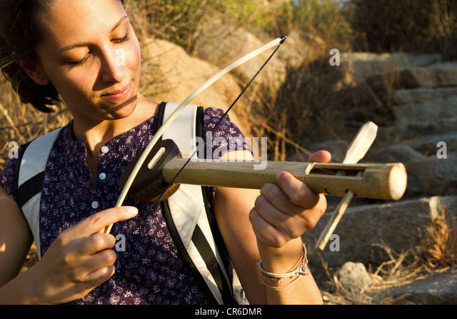 India, Goa, Young woman playing handmade wooden instrument - Stock Image