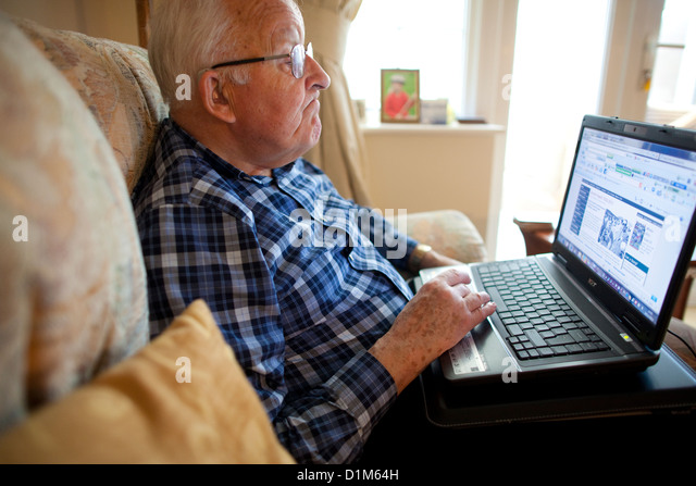 Elderly man using a laptop computer at home - Stock-Bilder