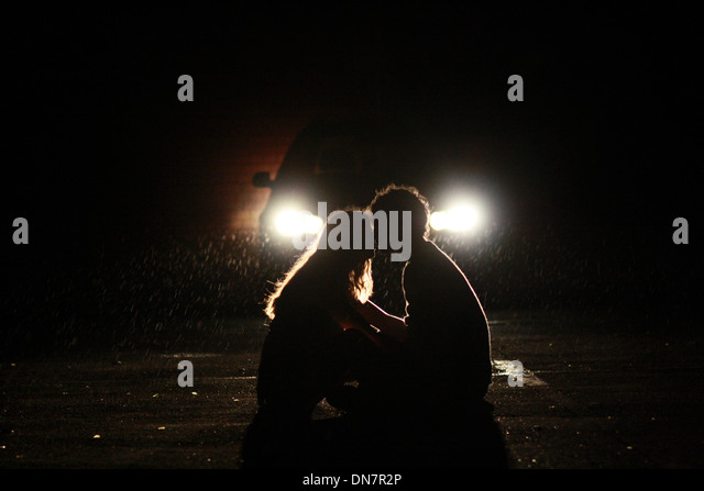 Loving couple sitting on the road in the headlights of a car - Stock Image