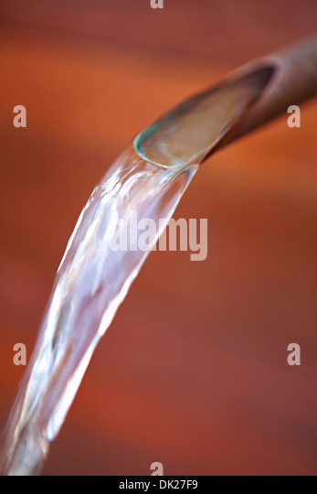 Close up of pure water pouring from spout - Stock Image