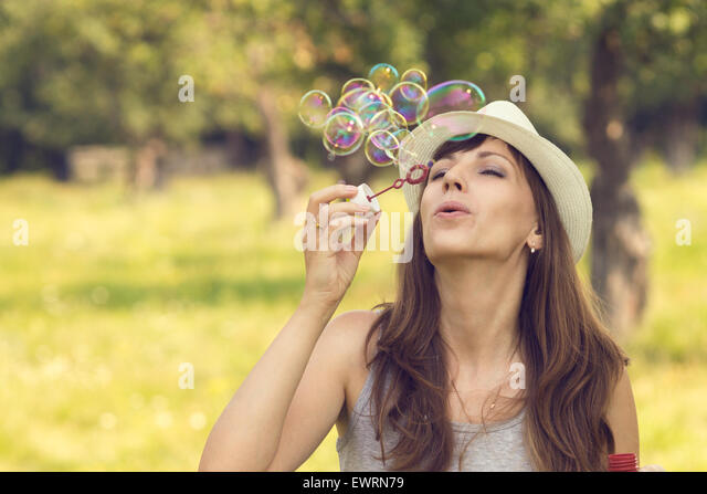 Young pretty caucasian woman having fun with blowing bubbles in summer park. Warm color toned image - Stock Image