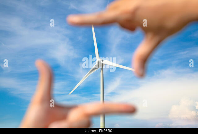 looking at windmill power generator with hand frame - Stock Image