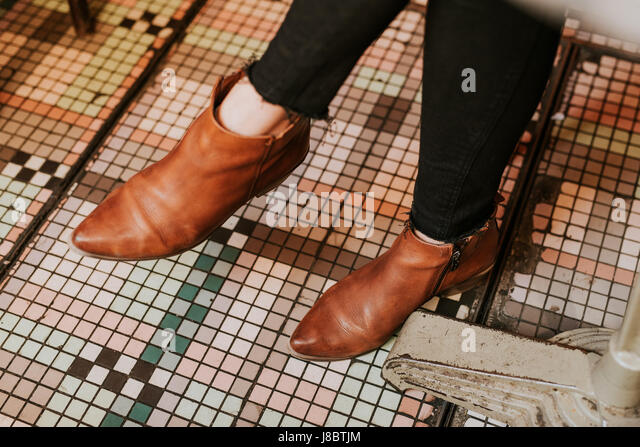 Detail of woman wearing brown leather boots - Stock Image