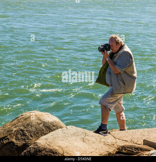 Photographer taking photograph while standing on rocky foreshore - Stock Image