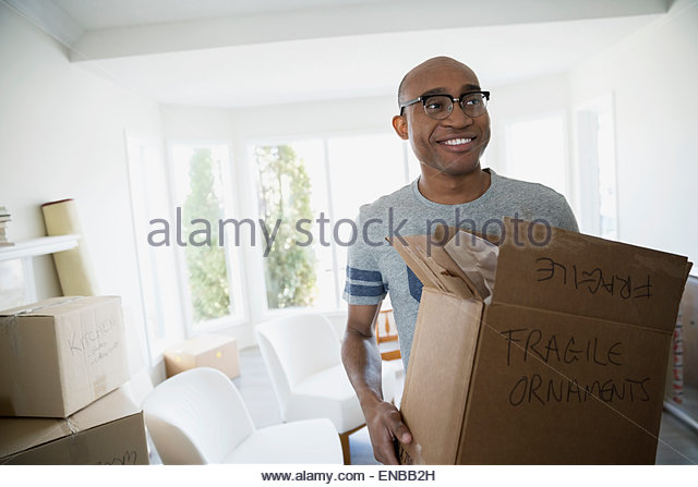 Smiling man carrying fragile moving box - Stock Image