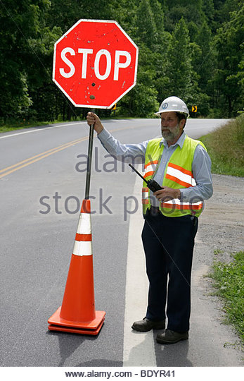 Virginia Lynchburg Route 501 stop sign construction crew man reflective safety vest traffic delay single lane traffic - Stock Image