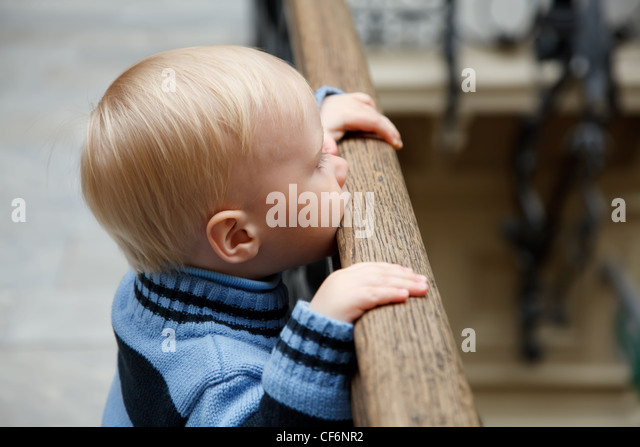 Little boy stands at fencing holding on to banister and looks downwards. - Stock Image