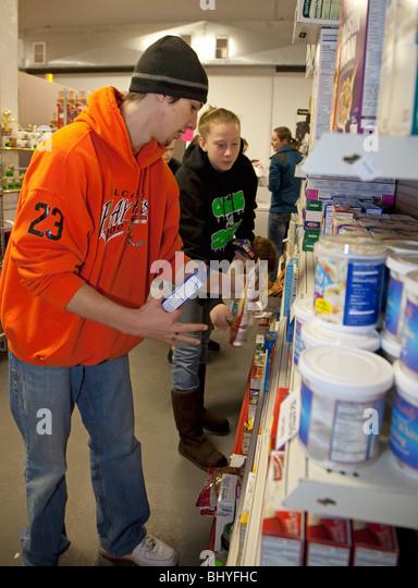 Teens Stock Shelves of Food Pantry - Stock Image