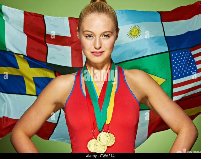 Young woman in front of international flags wearing medals - Stock-Bilder