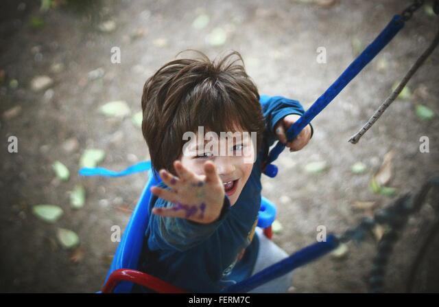 Portrait Of Boy Enjoying Swing In Park - Stock-Bilder