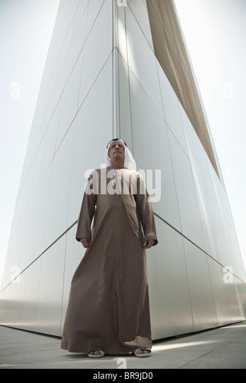 Middle eastern man by modern dubai building - Stock-Bilder